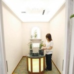 An employee adjusts flowers in a viewing room, where chilled encoffined corpses are delivered through